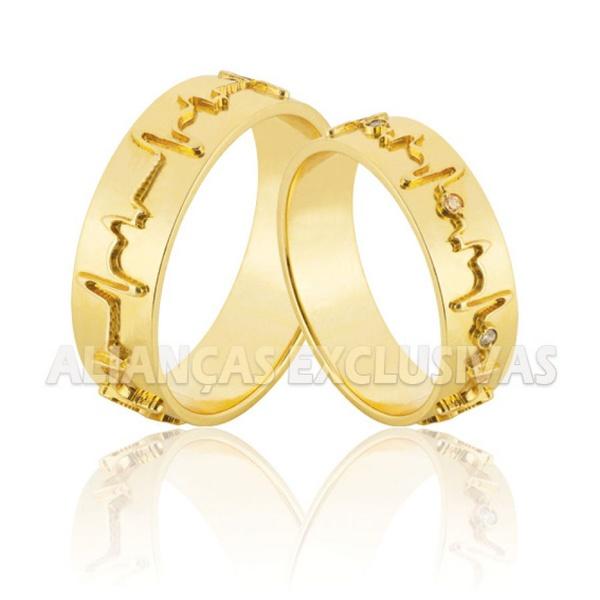 par de alianças grossas em ouro com detalhe de batimentos cardíacos